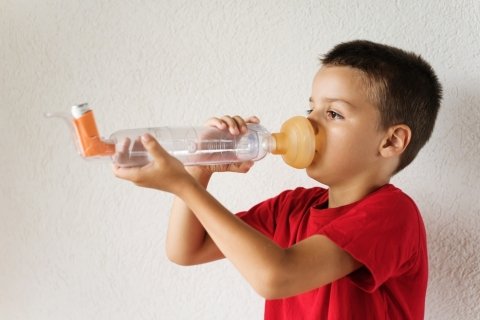 Boy using asthma puffer with spacer