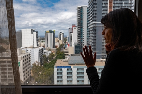 A woman peers out at the city from a hotel room some floors up