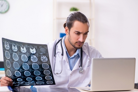 Doctor examines computer while holding scans of patient's brain