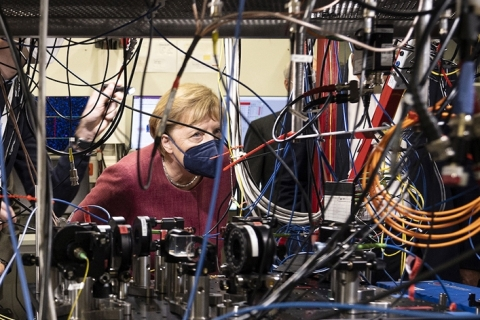 Angela Merkel peers out from a mass of wires and machinery
