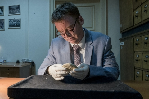 Dr Daniel Mansfield holds si.427 in gloved hands in a darkened museum storage room ng