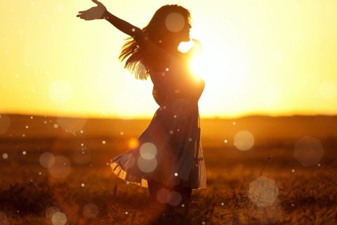 woman in sunshine with arms outstretched