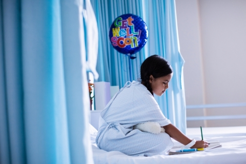 Girl in a hospital bed writing in a book