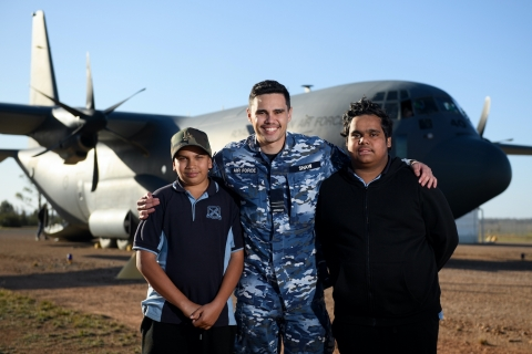 Tjapukai Shaw, RAAF Indigenous liaison officer, with two young Indigenous men in front of a large aircraft