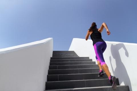 A woman runs up an outdoor staircase