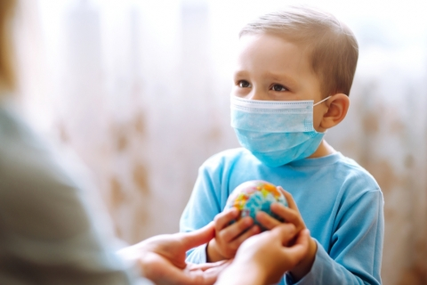 A child wearing a protective sterile medical mask with the parent holding a globe.