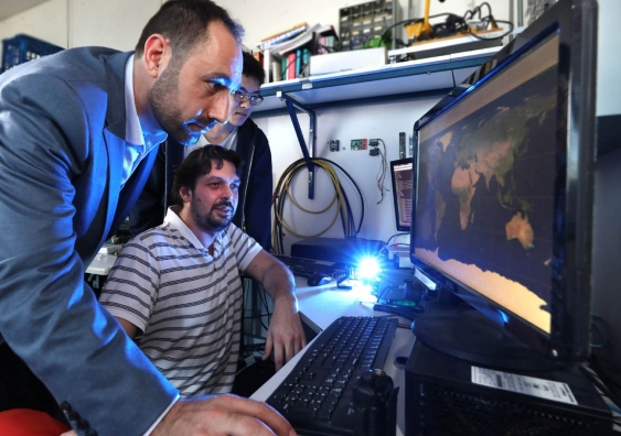 Elias Aboutanios (foreground), Timothy Guo (standing) and Alexander Kroh (seated) search for the missing UNSW-EC0 cubesat.