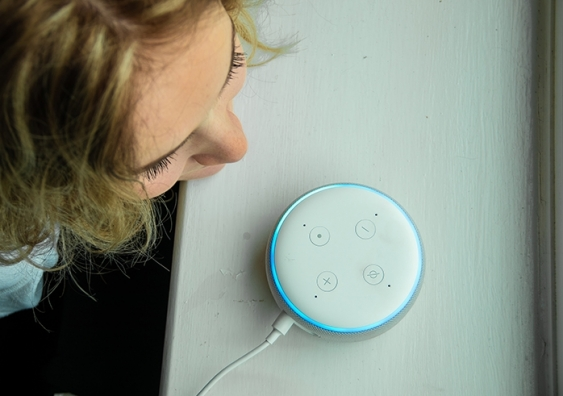 A young girl speaks over an Alexa virtual assistant device