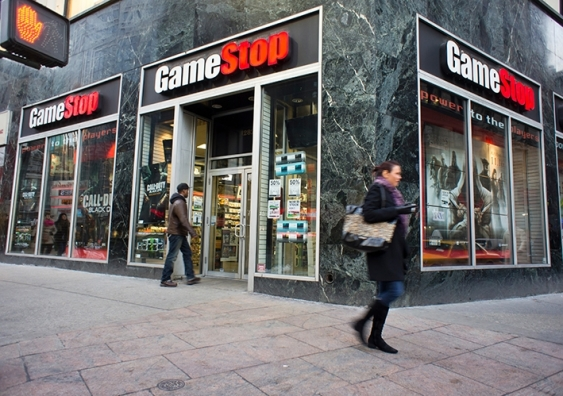 A person goes into a corner GameStop store as someone walks past
