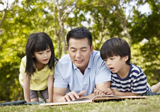A man reads from a book to two kids in outdoor setting