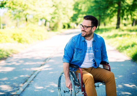 Man smiling in a wheelchair outdoors