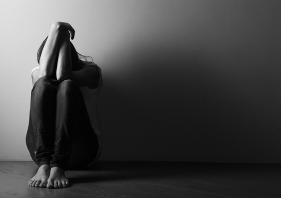 A person sitting down against the wall in a darkened room hiding their head in their hands