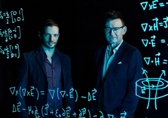 Dr Jarryd Pla and Prof. Andrew Dzurak look from behind a transparent screen showing mathematical workings