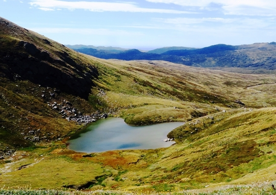 A view of Club Lake amid green hills and mountains on the horizon