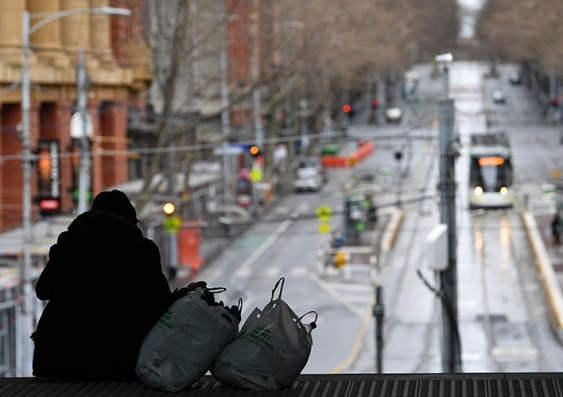 A homeless person sits on a platform overlooking a Melbourne street