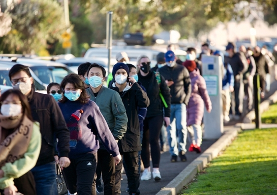 A long queue of masked people lined up to get their COVID-19 vaccination shots