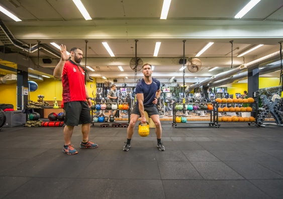 A trainer directing a man lifting a kettlebell