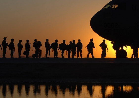 silhouette of soldiers boarding a plane