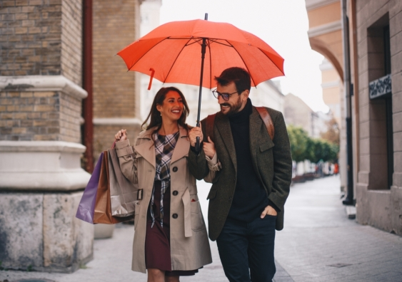 Man and woman holding shopping bags walk under an umbrella