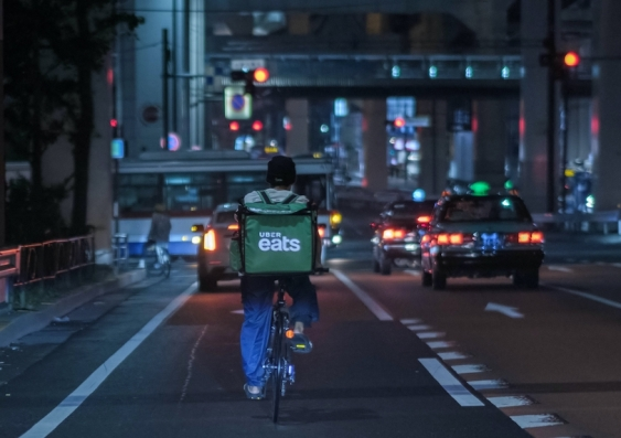 a delivery rider his bike on the road at night
