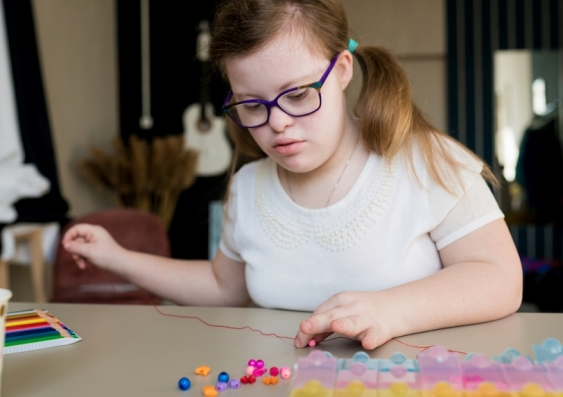 A disabled teen in glasses sits at a desk, beading a necklace