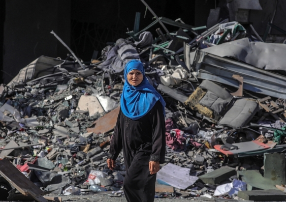 a palestinian women walks past the rubble of a building