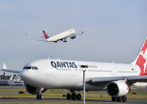 a qantas plane taxis on the tarmac with a delta flight taking off behind it