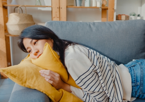 a woman lies on a lounge looking lethargic