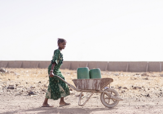 A young African girl carries buckets of water in a wheelbarrow across drought-stricken land.