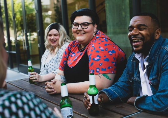 Group of friends laughing and chatting at an outdoor pub