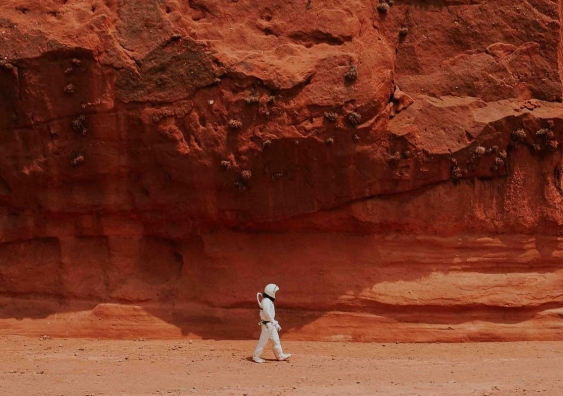 Astronaut walking in a red, rocky landscape