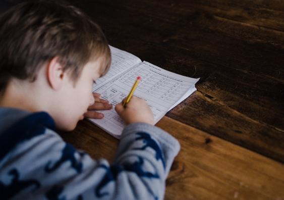 Boy filling out maths homework