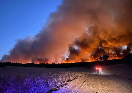 bushfires burning on the horizon at dusk on a farm