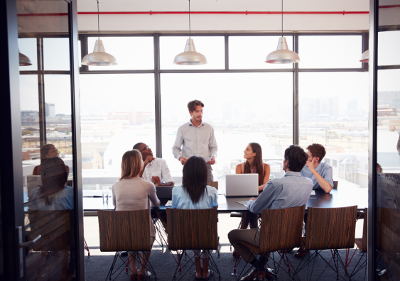 Office board meeting, person standing amongst a group of people sitting.