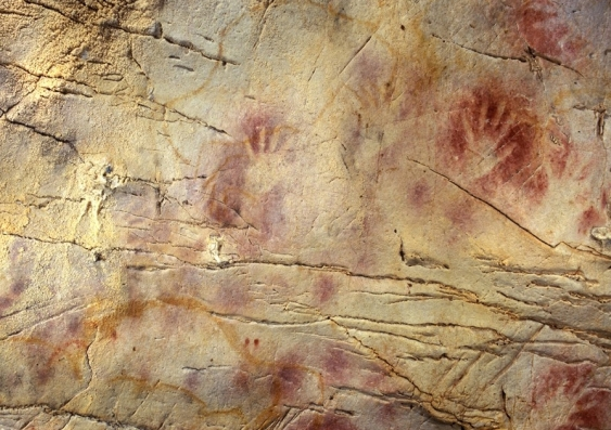 Handprints outlined by red ochre on a cave wall