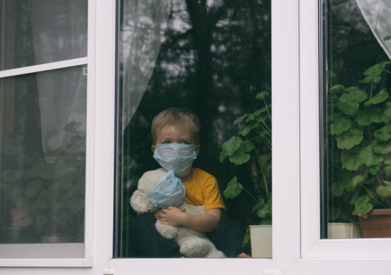 Child standing behind window looking out with mask on holding teddy which also has a mask on.