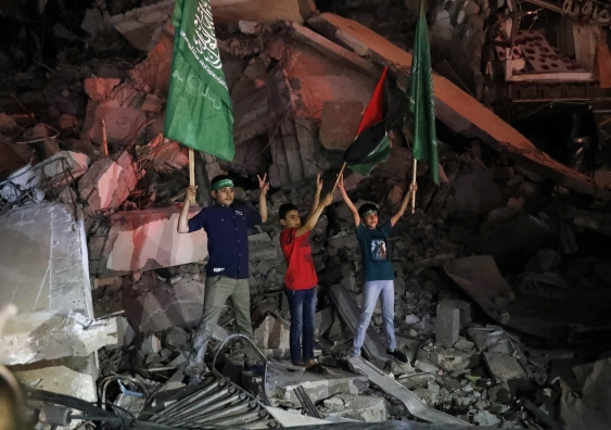 children hold flags in the rubble of a building