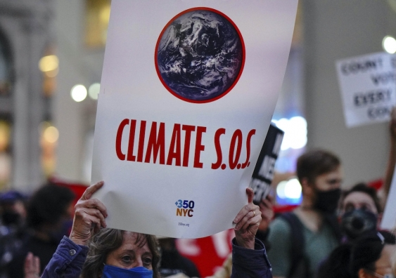 climate protester and sign