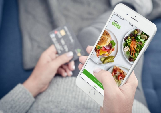 Close-up of woman holding phone ordering food on Uber Eats
