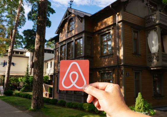 Airbnb logo being held up in front of a house