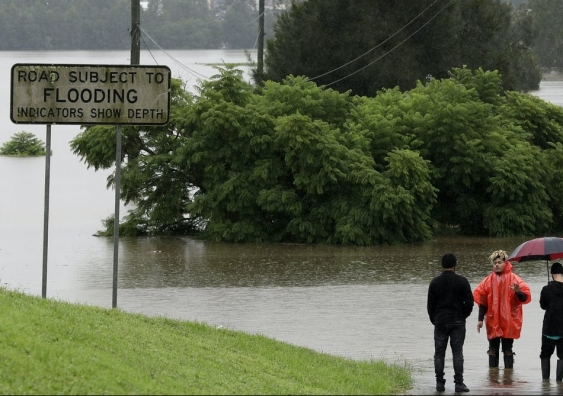 A flooded road with people standing by