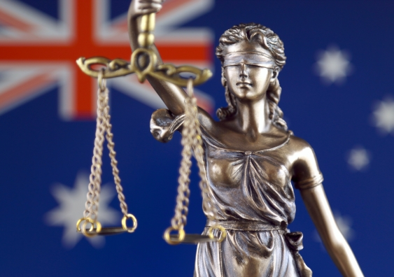 Scales of justice in front of Australian flag