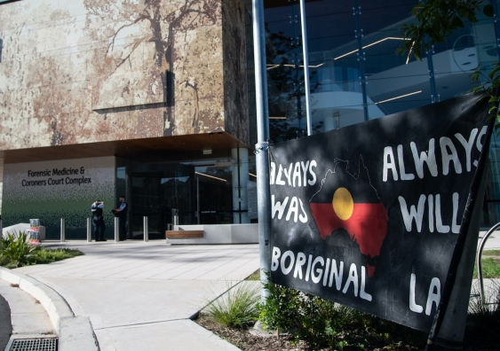 coronoers court with indigenous protest flag in foreground