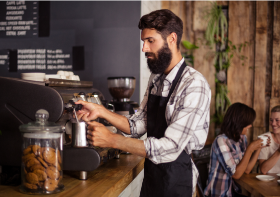 Bearded cafe worker making coffee on machine.