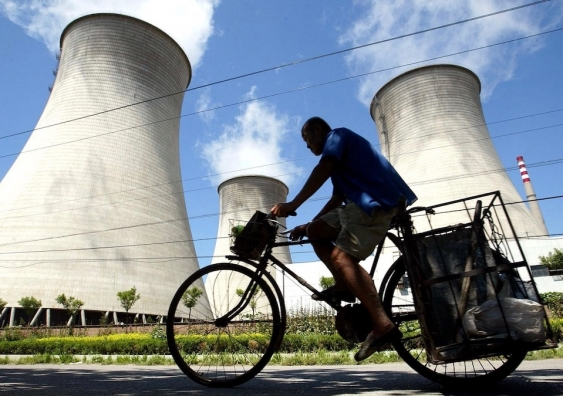 cyclist in front of cooling towers