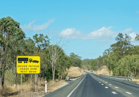 Sign says driver fatigue crash zone ahead on long highway