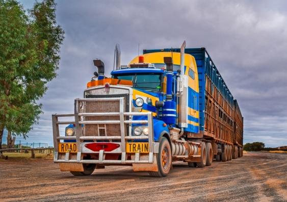 A road train drives down a dirt road