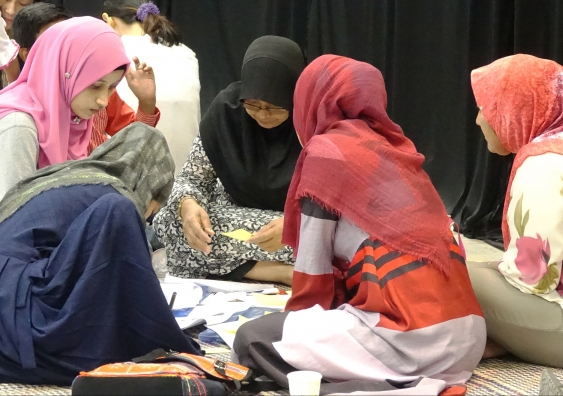 Refugee women in Malaysia seated on the floor doing group work