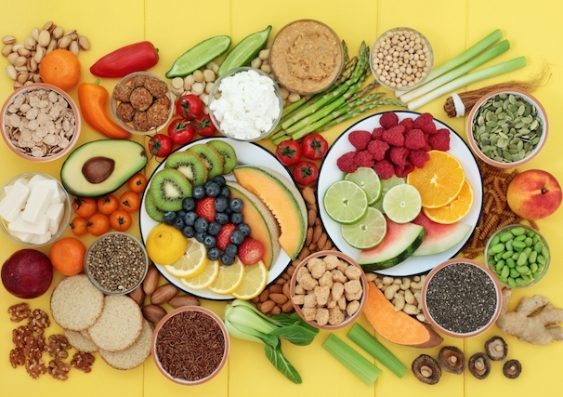 Fruits, vegetables, nuts and whole grains sit on a yellow background