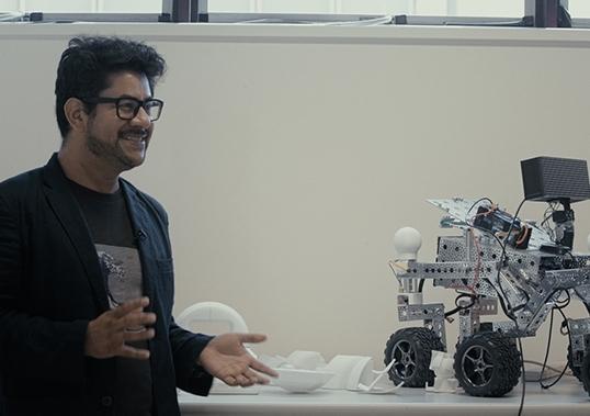 Dr Eduardo Benitez Sandoval beside a four-wheeled robot used in the Creative Robotics Lab
